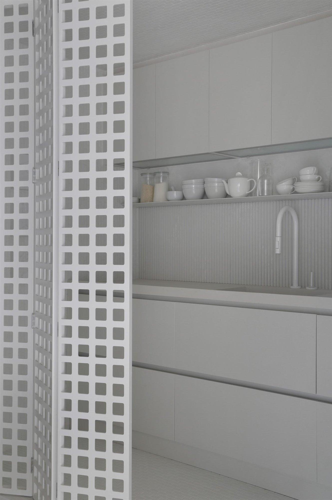 Detalle interior módulo cocina con puerta plegable perforada con motivos cuadrados, encimera, zona de aguas, estantes y amarios