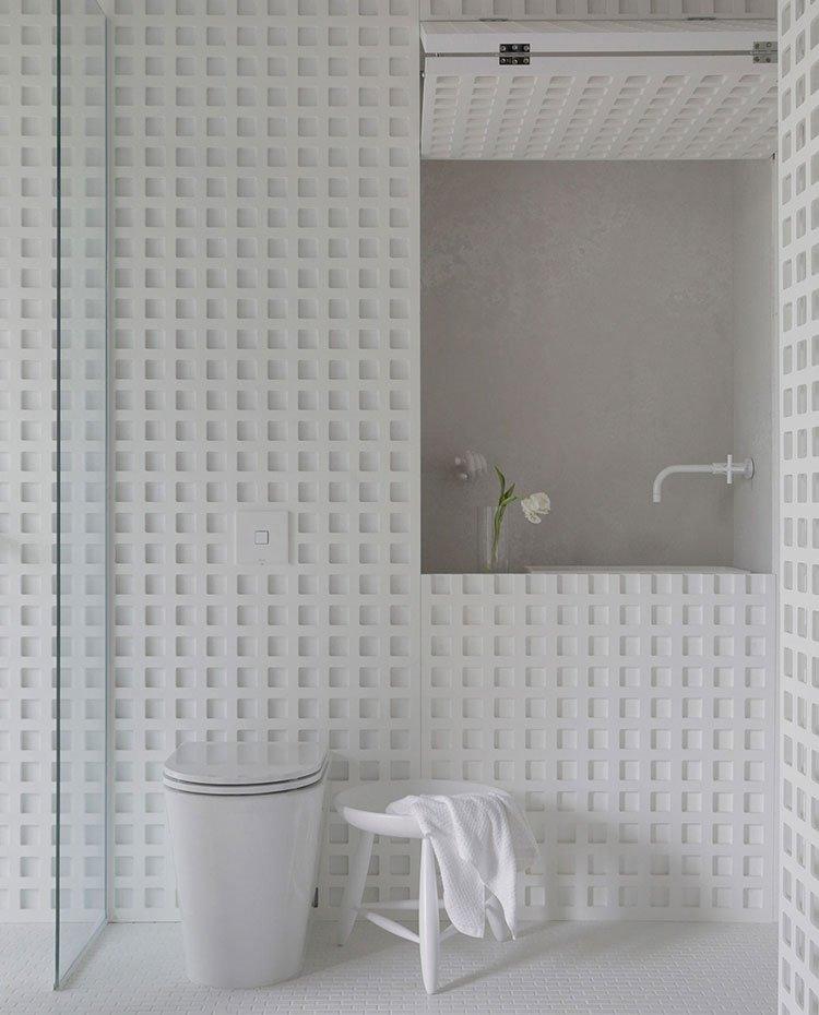 Detalle lavamanos de baño de habitación e inodoro, con grifería en blanco, lavamanos en hueco abierto junto a jarrón con flores blancas y estructura perforada con motivos geométricos