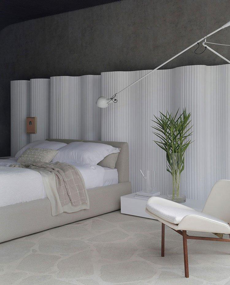 Dormitorio con trasera con una gran estructura blanca de formas curvas, butaca blanca con acabado de amdera, ropa de cama de tonos crudos, suelo de piedra