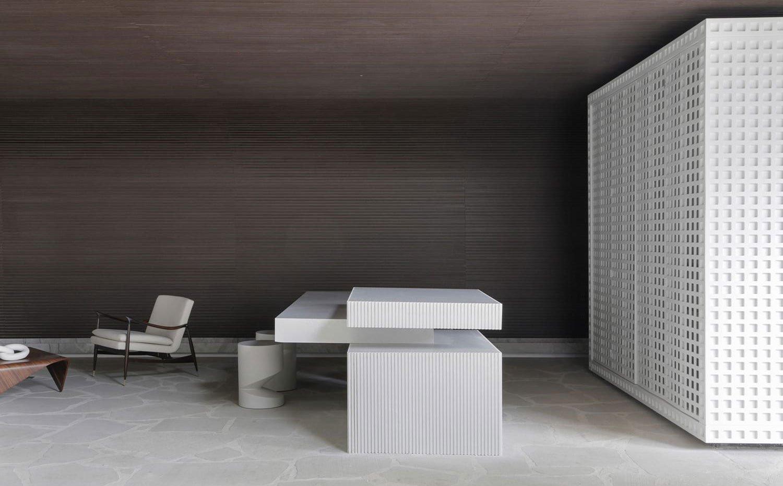 Isla de trabajo con office en cocina, todo en blanco, con mobiliario integrado en estructura independiente y cerrada de acero perforado, butaca en color crema y acabado madera y mesa de centro de madera