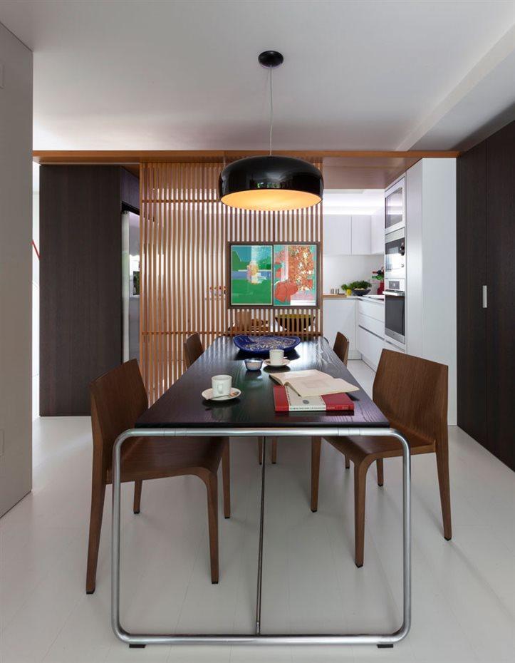 marbella10. La mampara de madera delimita el área de la cocina, abierta a la zona del comedor para favorecer la comunicación. Los tonos oscuros en ambos extremos enmarcan ambos espacios