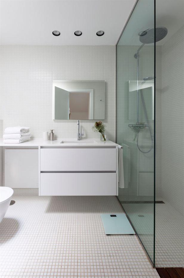 marbella34. El sentido práctico domina la planificación del baño. La ducha está separada mediante una única hoja de cristal fija. El lavabo se integra para facilitar su limpieza con un mueble suspendido bajo la encimera