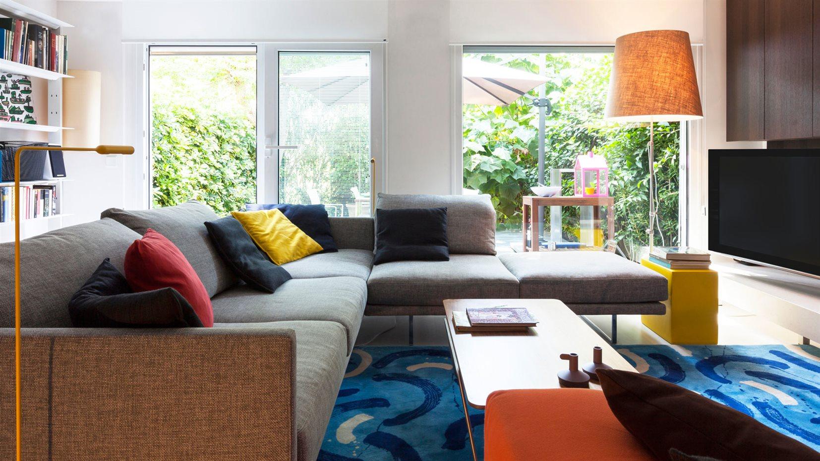 marbella40. La alfombra de inspiración marina, los cojines y los pequeños detalles iluminan la estancia de vitalidad y color. El sofá gris en ángulo preside la estancia y sirve de elemento integrador