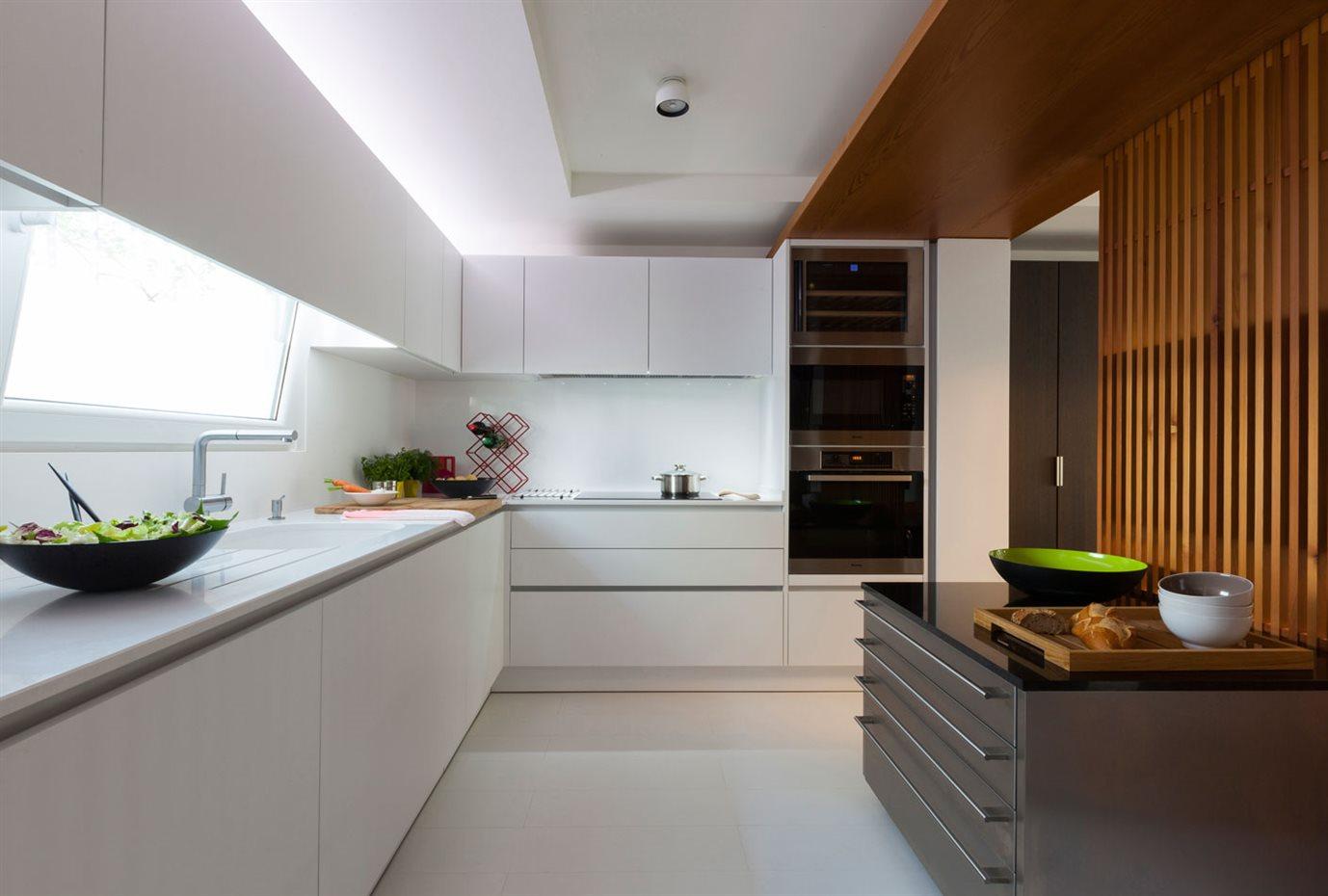 marbella4. La cocina es abierta en ambos extremos, favoreciendo la intercomunicación con el resto de la vivienda. La mampara corredera de listones de madera y dos islas auxiliares son los únicos elementos divisores