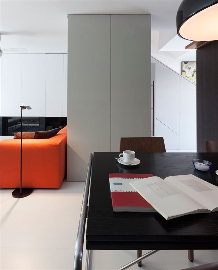 marbella8. En la zona de estar, un único sofá con alegre tapicería naranja es el contrapunto cromático de toda la vivienda en la que el color blanco y la madera oscura son los grandes protagonistas