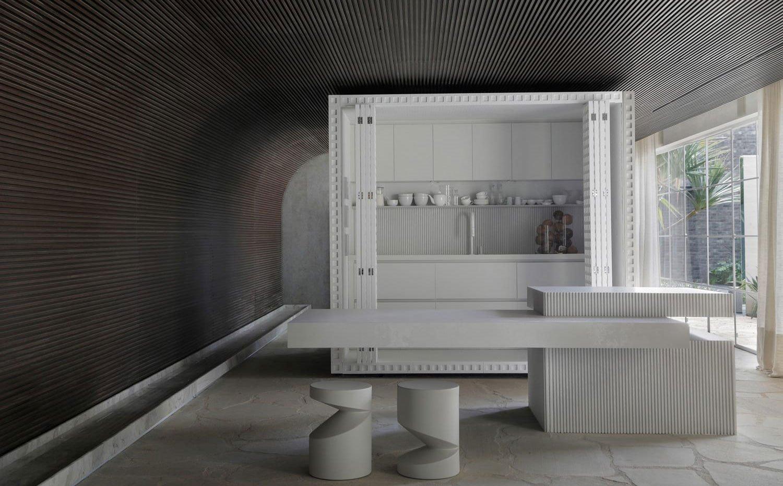 Módulo blanco con cocina integrada y puertas plegables, isla de trabajo con base blanca alistonada y encimera volada para office, dos taburetes blancos