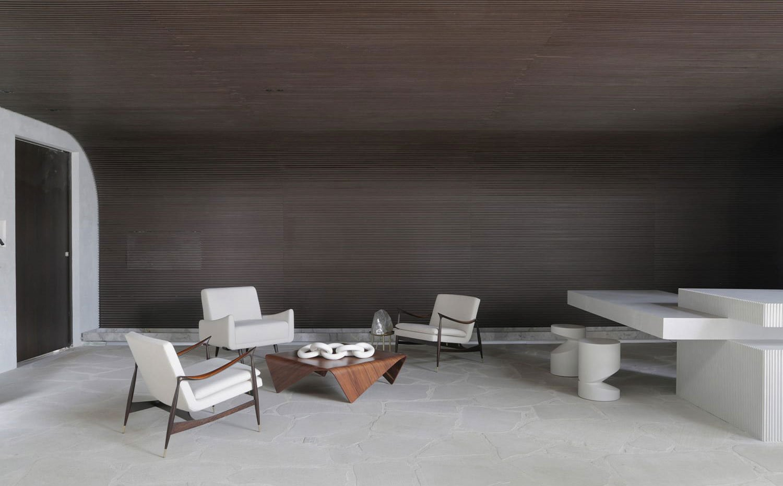 Puerta de acceso con marco en blanco, suelo de piedra, butacas en crema con estructura de madera oscura, mesa de centro de madera junto a isla de cocina y taburetes bajos en blanco