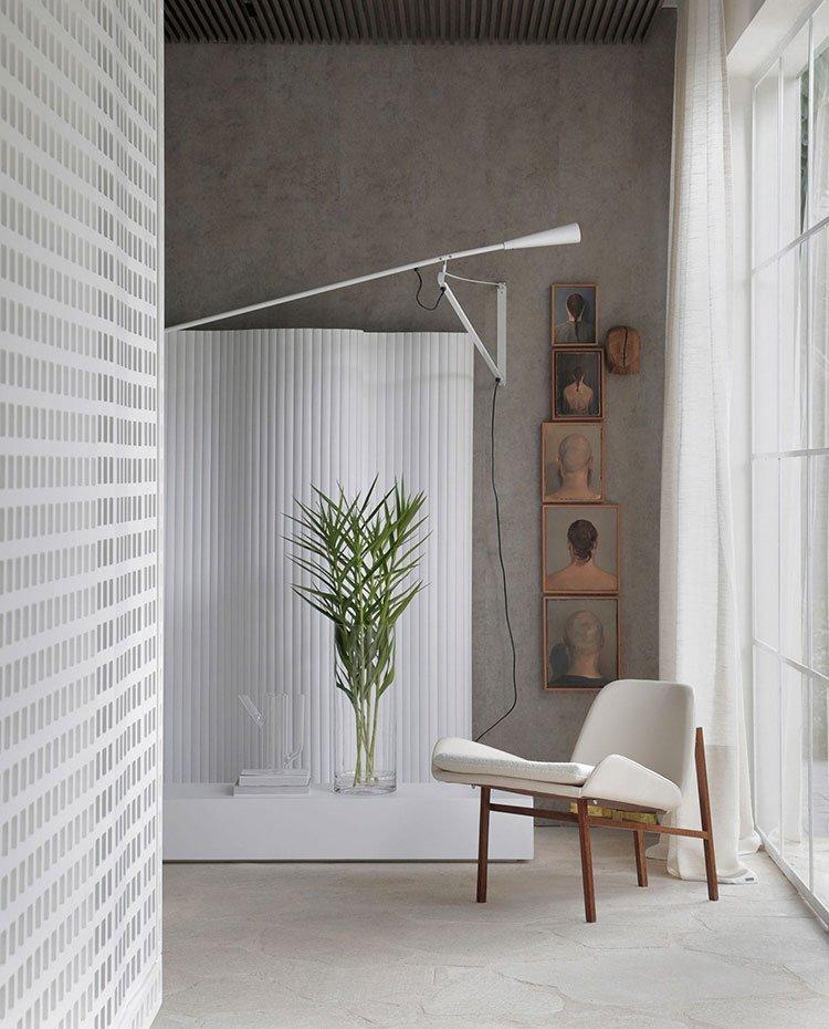 Rincón lectura con butaca en blanco y madera, aplique de pared en blanco a juego con biombo y mueble bajo, revestimiento de hormigón y piedra