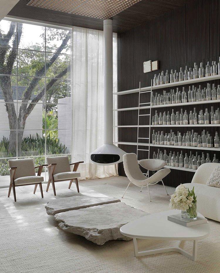 Salón con estantería de botellas de cristal, chimenea suspendida, butacas, sofá y mesa de centro en blanco, cerramiento acristalado con cortina blanca de techo a suelo