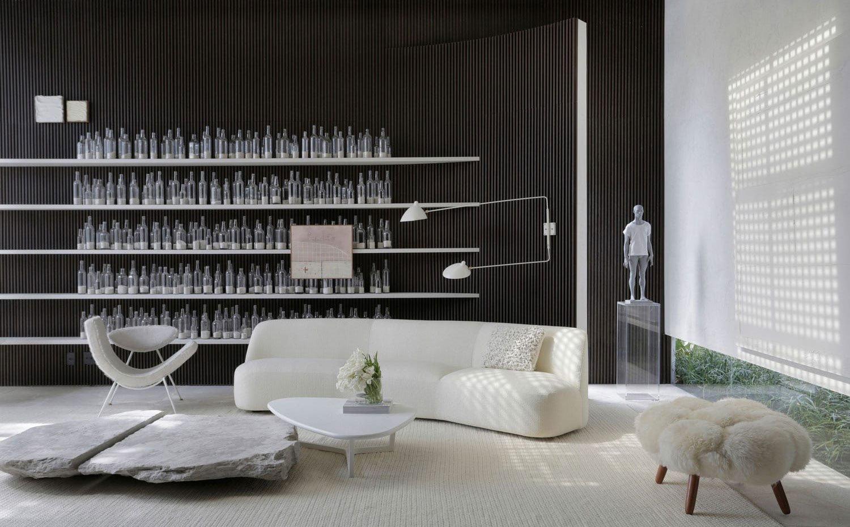 Zona de estar con mobiliario en blanco, estantería con botellas de cristal, escultura en gris sobre pedestal de metacrilato, pared alistonada