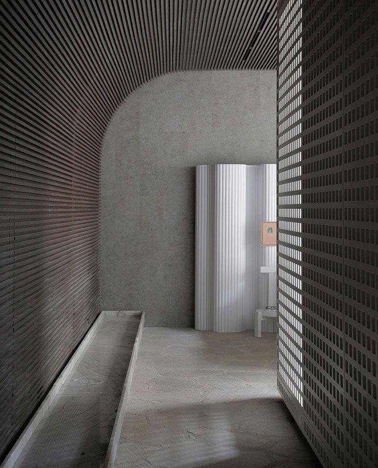 Zona de paso con suelo de hormigón, paredes con cantos curvos y alistonadas, biombo blanco, estrutura perforada translúcida